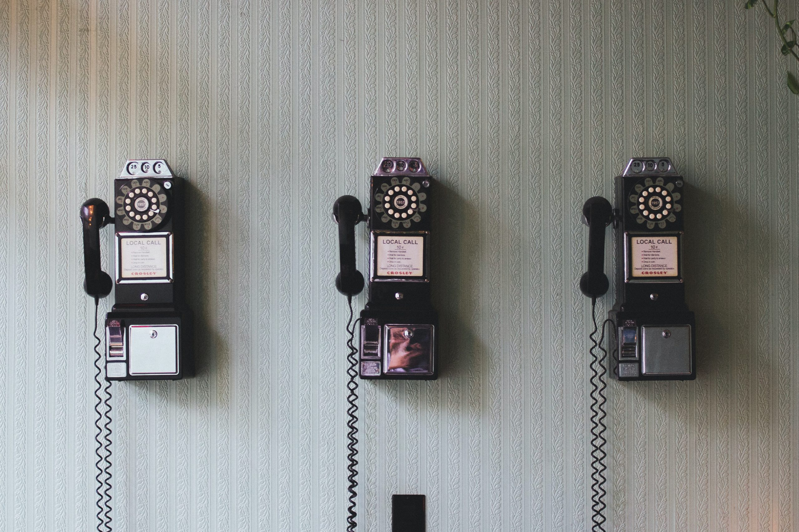 Three telephones hung on the wall